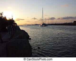 Sailing ships in port at sunset with red sky