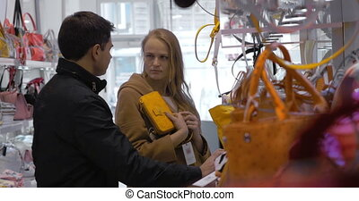 Family couple buying ladies handbag in the store - Young...