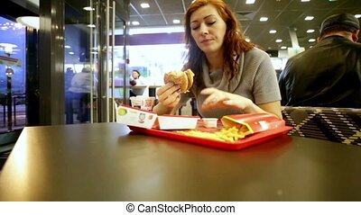 Pretty woman eating hamburger in fast food - Young woman...