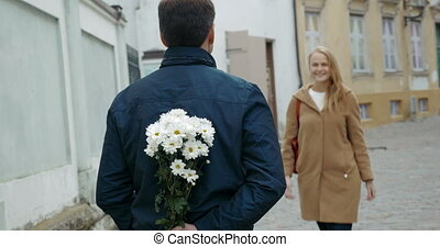 Man meeting beloved woman with flowers
