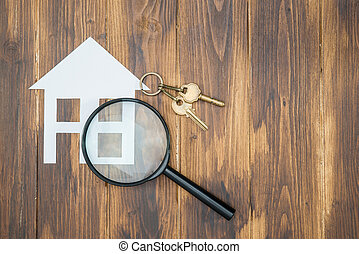 paper house and key with Magnifying Glass, House hunting on...