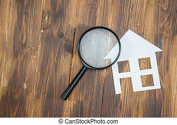paper house with Magnifying Glass, House hunting on wooden...