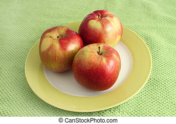 Stack of apples - Stack of three apples on a plate with a...