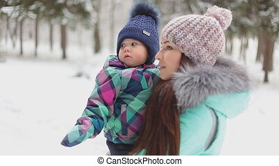 happy mother holding baby girl on the walk in winter snowy forest