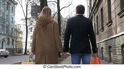 Young Couple With Shopping Bags - Back view of the young...