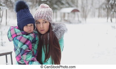 happy mother holding baby girl on the walk in winter snowy...