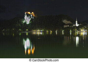 Famous castle and St. Martins Parish Church in the night on Bled lake