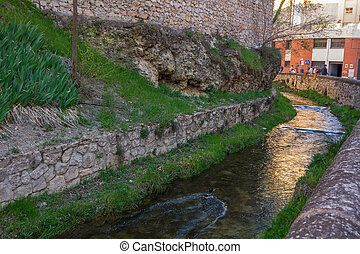 Small water canal crosses the city of Cuenca, Spain