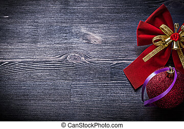 Christmas bow ball on wooden board holidays concept