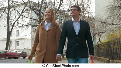 Elegant man and woman walking after shopping - Steadicam...