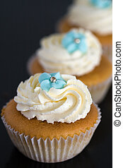 Cupcakes decorated with whipped cream and blue sugar flowers