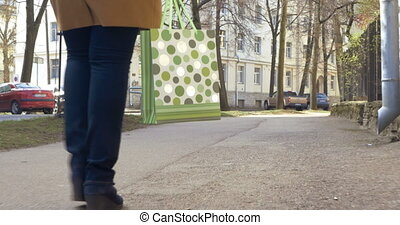 Woman Walking with Green Shopping Bag - Steadicam low-angle...