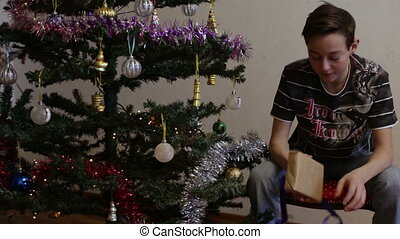 Teenager boy opening Christmas gift