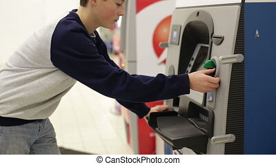 Teen inserts bank card into the ATM and enters PIN -...