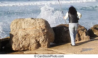 Woman with a fishing rod on the shore