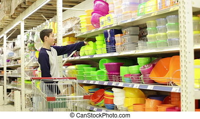 Teen boy in store selects a container for food - Teenager...