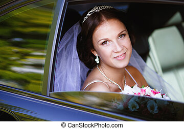 Bride in a car in her wedding day