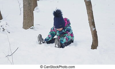 Little girl playing with snow in park