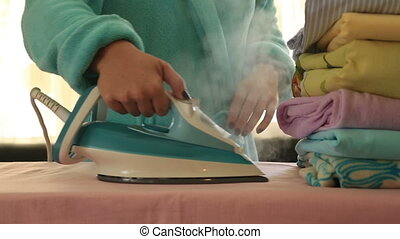 Woman ironing clothes in a utility room