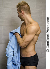 Handsome semi-naked young man in bathroom with towel -...