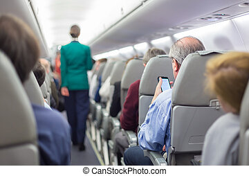 Stewardessand passengers on commercial airplane - Interior...