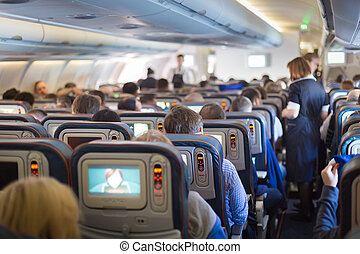 Stewardessand passengers on commercial airplane. - Interior...