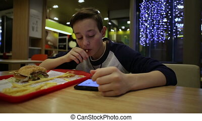Teen Eating French Fries and Using Smartphone - Teenager...