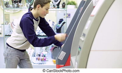 Teenager boy Using Cash Machine - Teenager boy Using ATM...