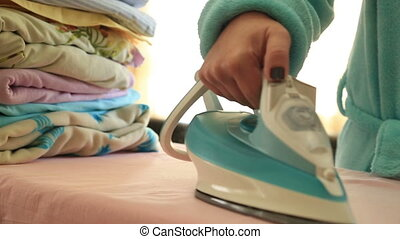 Woman ironing clothes with a steaming iron