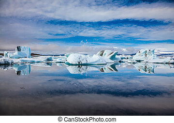 Ice magnificence. Floating ice and clouds are reflected in...