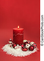 red candle with christmas baubles