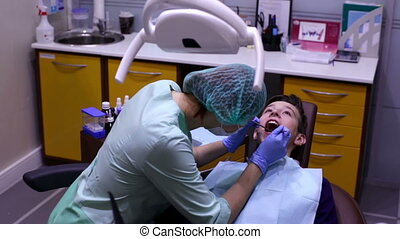 The dentist examines the teeth teenager - Dentist examining...