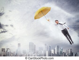 To fly high - Businessman flying with an umbrella over city