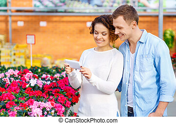 Couple taking pictures of blooming flowers. - Taking...