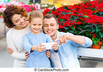 Young family taking selfies in the greenhouse - Selfies to...