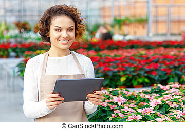 Smiling florist holding a tablet. - Working with devices....