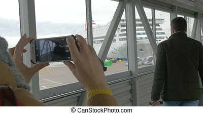 Woman with cell taking picture of a man in dockyard - Woman...