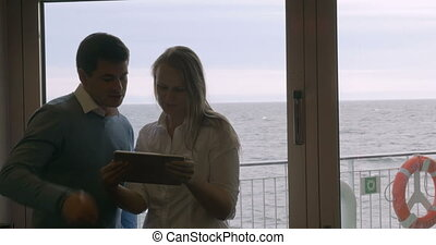 Young couple using tablet PC on board the ship
