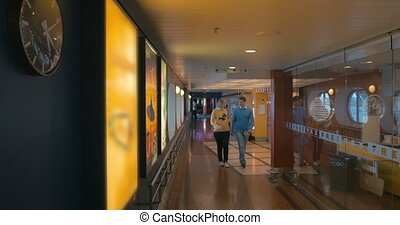 Couple passing by tax free store on the ship - Young man and...