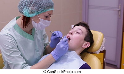 The boy on reception at the dentist - Dentist examining...