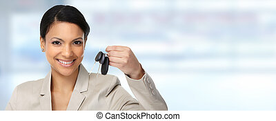 Auto dealer woman with a car key.