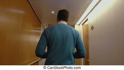 Man walking along the hotel corridor back to the camera