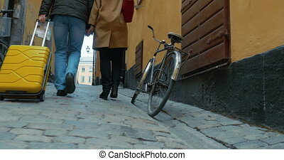 Sightseeing on foot in Europe - Man and woman with rolling...
