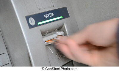 Man's hand inserting and removing a bank card at an ATM. -...