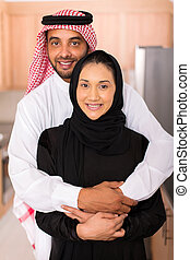 muslim man hugging his wife - portrait of happy muslim man...