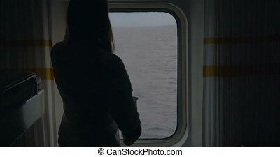 Girl opening blind in cabin to look at the sea - Young woman...