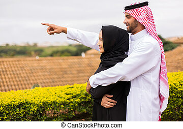 young middle eastern couple pointing - cheerful young middle...
