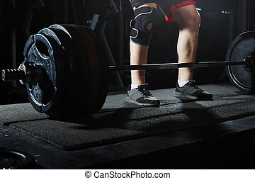 Weightlifting - Man at the heavy barbell in fitness club....