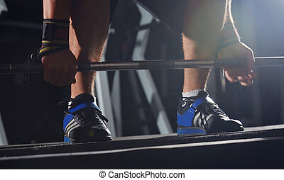Weightlifting - Hands of man ready to lift barbell at...