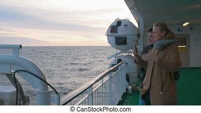 Young couple making phone selfie on shipboard